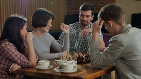 Young couple playing chess indoor with friends stock video footage