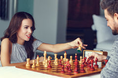 Young couple playing chess indoor Stock Images