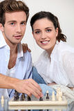 Young couple playing chess Stock Photos