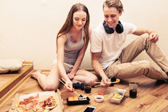 Young couple playing computer game home together, hobby, addiction eat Royalty Free Stock Image