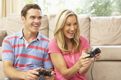 Young Couple Playing Computer Game On Sofa At Home. Having Fun Stock Photo