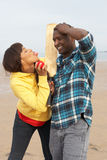 Young Couple Playing Cricket On Beach Holiday Stock Photos