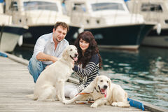 Young couple playing with a dog in the harbor. Young couple with dog posing at historical town sunny day. Couple playing with their dog in harbor Stock Photos