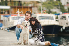 Young couple playing with a dog in the harbor. Young couple with dog posing at historical town sunny day. Couple playing with their dog in harbor Stock Images