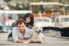Young couple playing with a dog in the harbor. Young couple with dog posing at historical town sunny day. Couple playing with their dog in harbor Royalty Free Stock Image