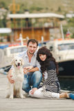 Young couple playing with a dog in the harbor. Young couple with dog posing at historical town sunny day. Couple playing with their dog in harbor Stock Photo