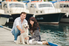 Young couple playing with a dog in the harbor. Young couple with dog posing at historical town sunny day. Couple playing with their dog in harbor Royalty Free Stock Images