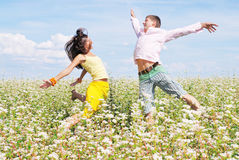 Young couple playing on field of flowers. Young couple on field of flowers in sunny day Royalty Free Stock Images