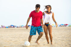 Young couple playing football on the beach. At sunset Royalty Free Stock Photo