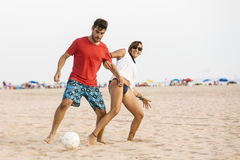 Young couple playing football on the beach Royalty Free Stock Images