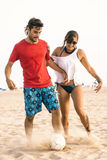 Young couple playing football on the beach Stock Images