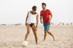 Young couple playing football on the beach Royalty Free Stock Photo