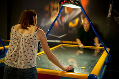 Young couple playing a game of air hockey