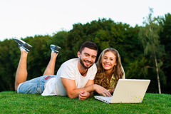 Young couple playing in games on laptop. Internet outdoors. Gambling games. Lovers resting in a park with a computer. Weekend outdoors Royalty Free Stock Photo
