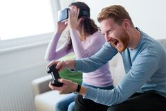 Young couple playing games with virtual reality headset. Young happy couple playing games with virtual reality headset together Royalty Free Stock Photography