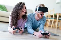 Young couple playing games with virtual reality headset. Young happy couple playing games with virtual reality headset together Stock Image