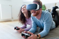 Young couple playing games with virtual reality headset. Young happy couple playing games with virtual reality headset together Royalty Free Stock Photos