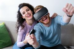 Young couple playing games with virtual reality headset. Young happy couple playing games with virtual reality headset together Stock Images
