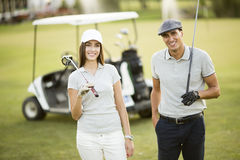 Young couple playing golf Stock Images