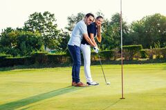 Young couple playing golf. Personal trainer giving lesson on golf course.