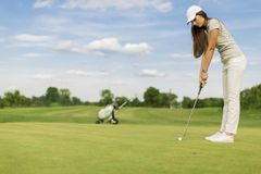 Young couple playing golf. Young woman playing golf at sunny day Stock Photo