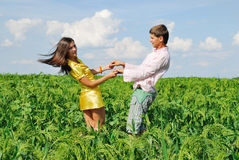Young couple playing on green field. In sunny day Royalty Free Stock Photo