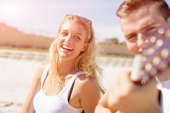 Young couple playing guitar on beach in love Royalty Free Stock Photos