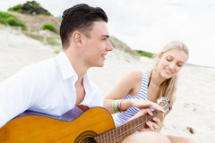 Young couple playing guitar on beach in love Stock Images