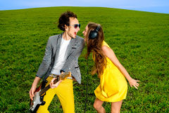 Young couple playing on guitar and enjoying the music, they shou Royalty Free Stock Photo