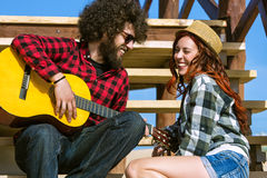 Young couple playing guitar stock photography