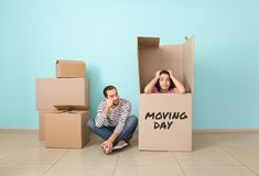 Young couple playing with huge box indoors. Moving into new house stock photos