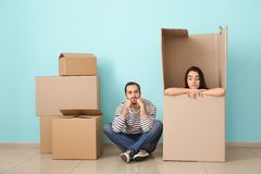 Young couple playing with huge box indoors. Moving into new house stock image