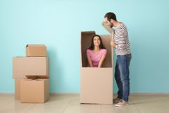 Young couple playing with huge box indoors. Moving into new house royalty free stock photo