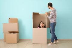 Young couple playing with huge box indoors. Moving into new house royalty free stock image