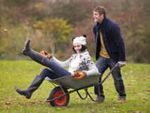 Young Couple Playing In Wheelbarrow Royalty Free Stock Images
