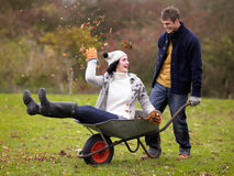 Young Couple Playing In Wheelbarrow Royalty Free Stock Photo