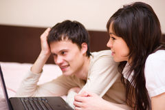 Young couple is playing on laptop. Indoor shoot Royalty Free Stock Image