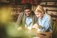 Leisure game at cafe. Happy couple. Young couple playing leisure games together at cafe and talking Royalty Free Stock Photo