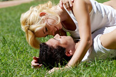 Young couple playing at park in grass Royalty Free Stock Image