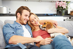 Young Couple Playing With Pet Dog At Home. Relaxing On Sofa Stock Photography