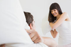 Young couple playing pillow fight Stock Photos