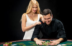 Young couple playing poker. Man taking poker chips after winning Stock Photos
