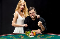 Young couple playing poker. Man taking poker chips after winning Royalty Free Stock Photos