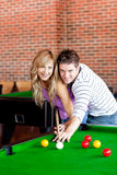 Young couple playing pool. In a club Royalty Free Stock Photo