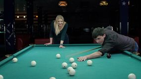 Young couple playing pool in a bar. Slow motion. Young couple playing pool in a bar. The guy could not hit the cue. Slow motion stock video footage