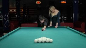 Young couple playing pool in entertainment center. Strike young man cue. Slow motion stock video footage