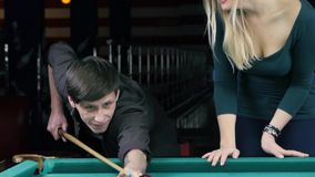 Young couple playing pool in entertainment center. Strike young man cue. Slow motion stock footage