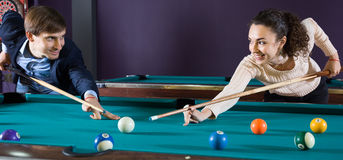 Young couple playing pool looking at each other. Smiling young couple playing pool looking at each other Royalty Free Stock Images