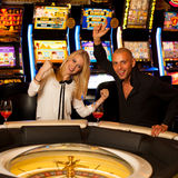 Young couple playing roulette in casino betting and winning Stock Photos