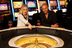 Young couple playing roulette in casino betting and winning Royalty Free Stock Images